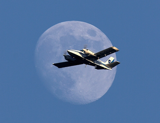 Piper Seneca flying in front of the moon